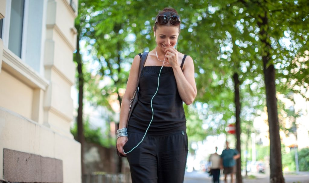 woman with earbuds, walking down a street