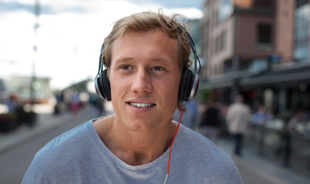 man with headphones, blurry buildings in the background