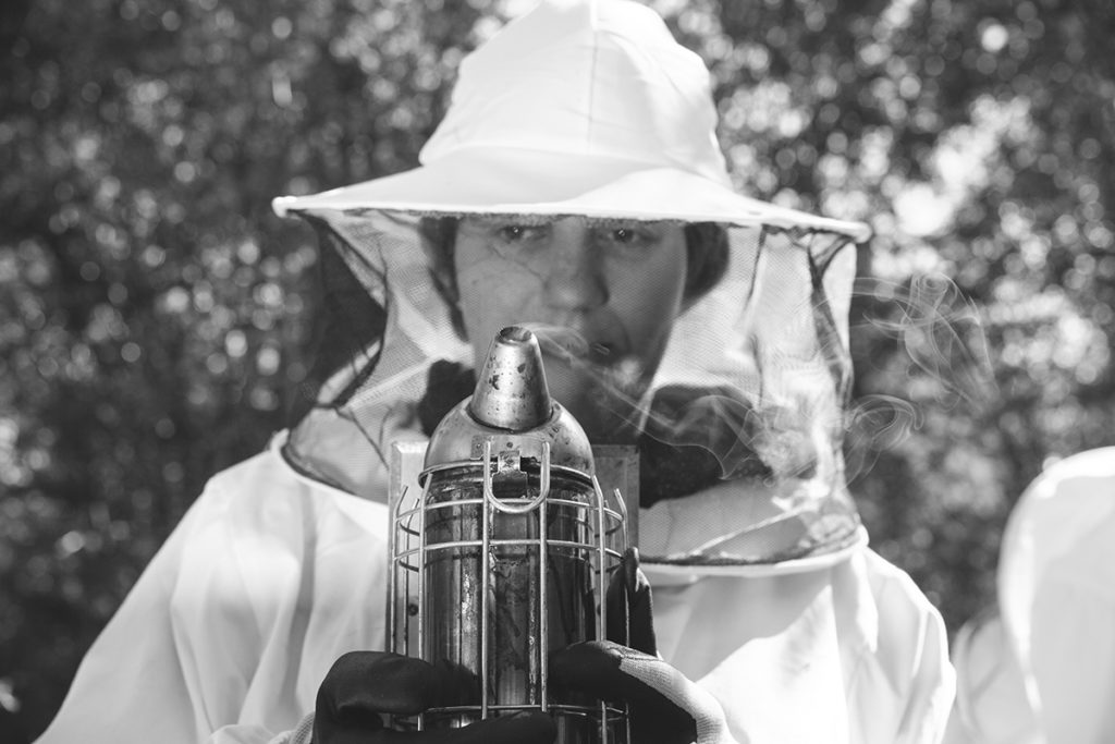 Someone in a beekeeper's costume holding an apparatus of some kind