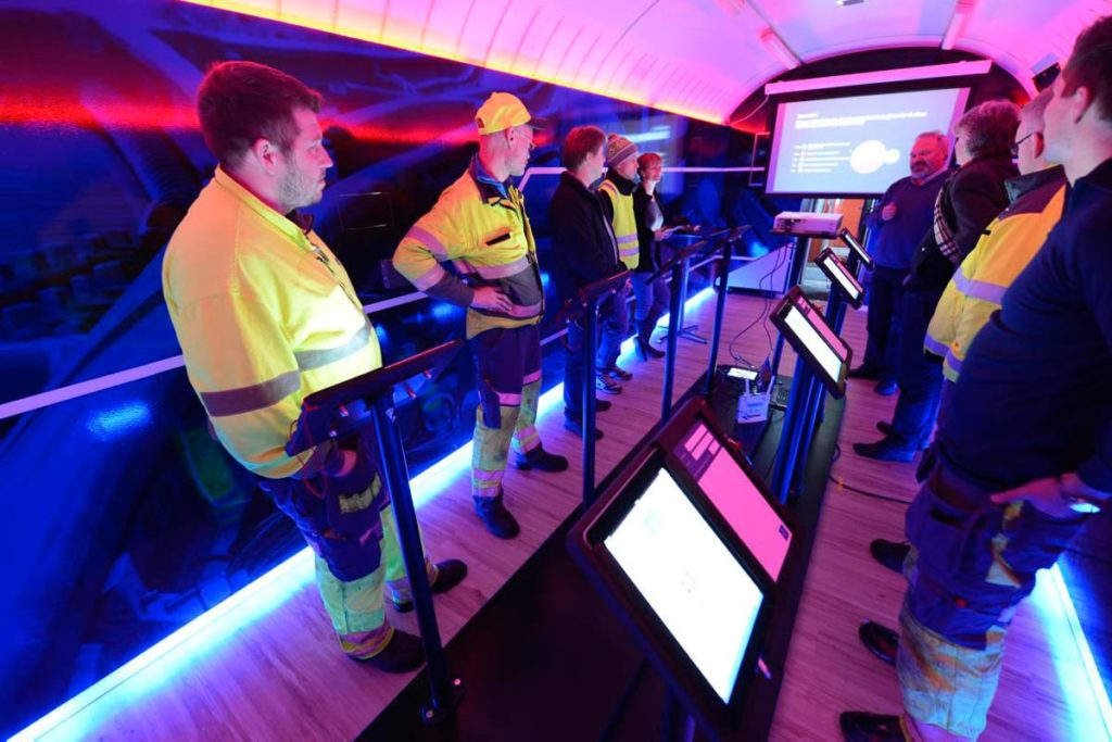 people in high-visibility clothing standing inside one of the customised train cars
