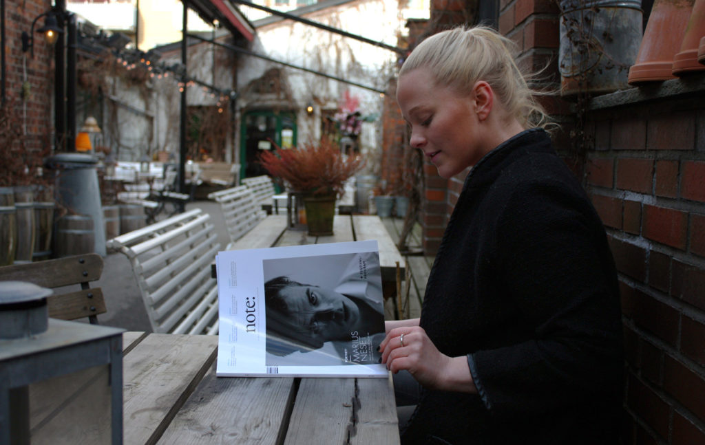 Woman sitting in a café reading Note magazine