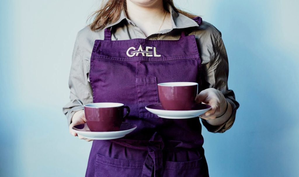 Woman in an apron holding to cups and saucers